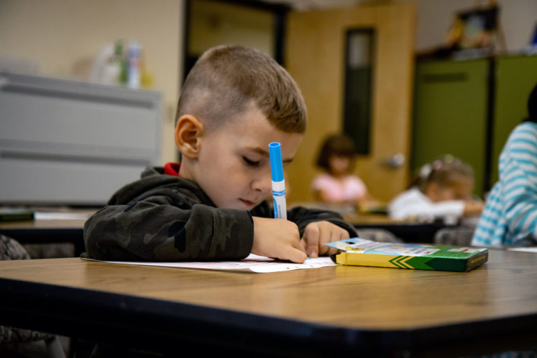 young school boy coloring with markers