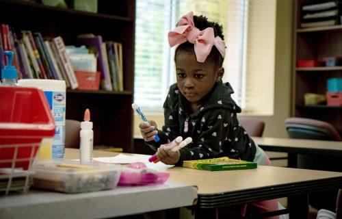 preschool girl with art supplies